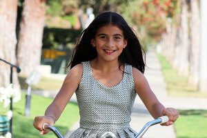 Middle school gril riding bike.